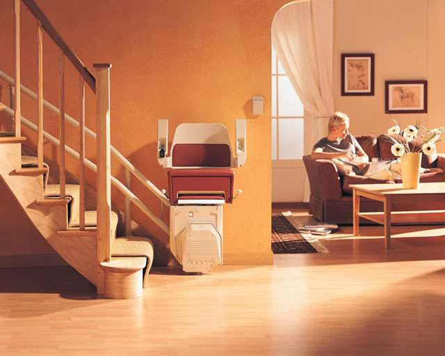 The Stannah Sarum 260 series red stair lift shown parked at the bottom of the stairs, with the arm rests, seat, and foot rest all in the up position, providing easy access to the stairs for people who do not need to use the stairlift.