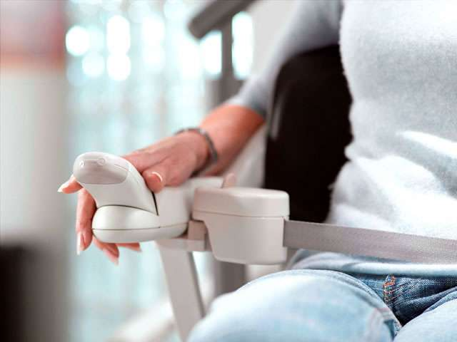 Close-up view of female user with hand on armrest controls, with seatbelt in locked position, on Stannah Solus 260 series Solus stair lift with brown upholstery.