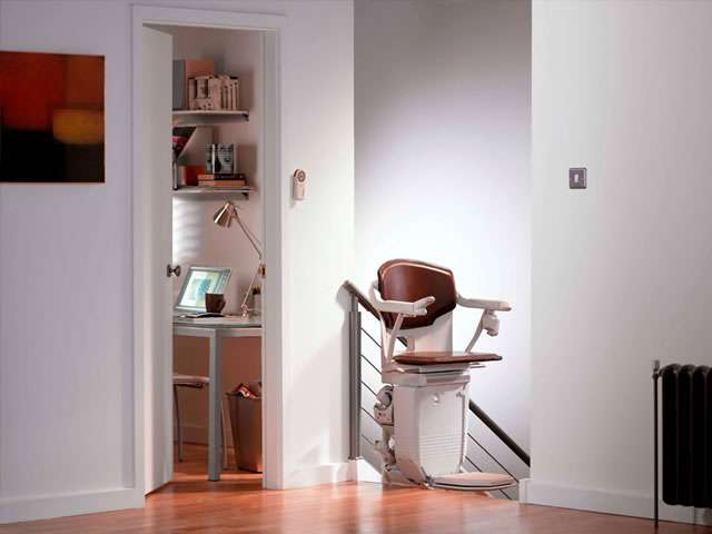 A Stannah 260 series Solus brown coloured upholstery stair lift shown parked at the top of the stairs with the chair facing sideways to the stairs.