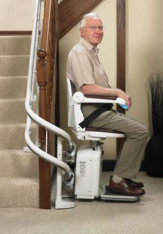 A smiling elderly male user is sitting on a Handicare 2000 brown coloured upholstery stair lift, with hand on the arm rest joystick control, and seatbelt on, about to go up the stairs using the stairlift.