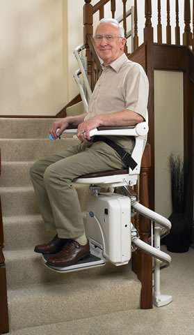 A smiling elderly male user is sitting on a Handicare 2000 brown coloured upholstery stair lift as it travels up the stairs passed the first bend or curve.