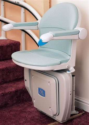 Handicare 2000 stair lift in light blue colour, parked at the bottom of the stairs, with armrests and seat in the down position, and footrest in the up position.