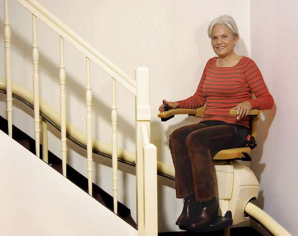 A smiling female user sat on a Handicare Van Gogh stair lift as it travels down the stairs going around a curve / bend.