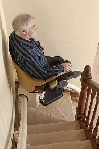 A side view of an elderly male user sitting on a Handicare Van Gogh stair lift as it travels up steep stairs.