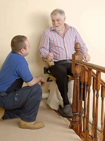 A smiling elderly male user sitting on a Handicare Van Gogh stairlift chair talking with a stair lift engineer at the top of the stairs.