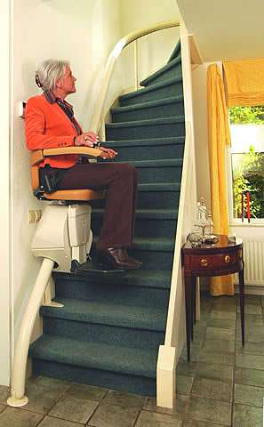 An elderly female user going upstairs on a Handicare Van Gogh stair lift as it curves around the staircase.