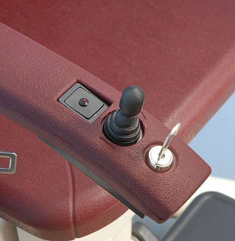 A close-up photo of the armrest of a brown-coloured Handicare stairlft, showing the power indicator, joystick control, and key lock with key inserted.