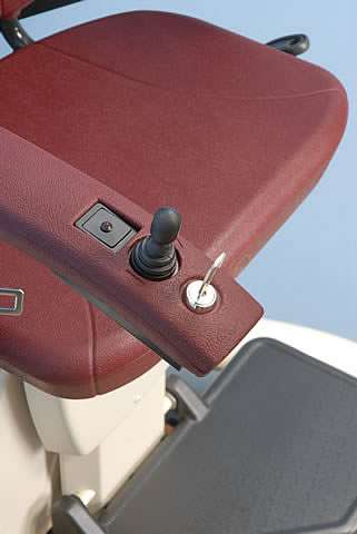 A different angle close-up photo of the brown coloured armrest of a Handicare stairlft, showing the power indicator, joystick control, and key lock with key inserted.