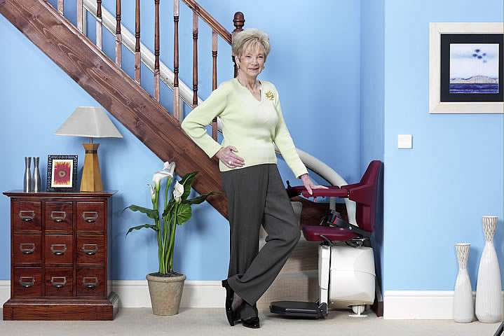 A female user standing next to a Handicare Van Gogh stairlift, with hand on armrest, situated at the bottom of the stairs.