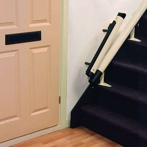 A photo of the bottom of stairs stairlift rail showing how the last stairlift rail section at the bottom of the stairs is retracted back over and above the stairlift rail, to prevent blocking the adjacent door access.