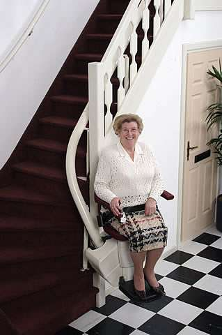A photo of smiling elderly female user sitting on a Handicare Rembrandt stair lift at the bottom of the stairs.