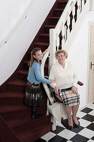 A photo of smiling elderly female user sitting on a Handicare Rembrandt stair lift at the bottom of the stairs talking with younger family member.