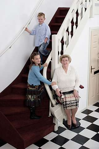 A photo of smiling elderly female user sitting on a Handicare Rembrandt stair lift at the bottom of the stairs talking with two younger family members on the stairs.