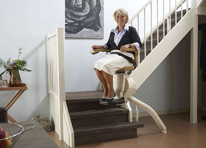A female user riding on a Handicare Rembrandt stair lift near the bottom of the stairs, as it approaches a bend in the stairs.