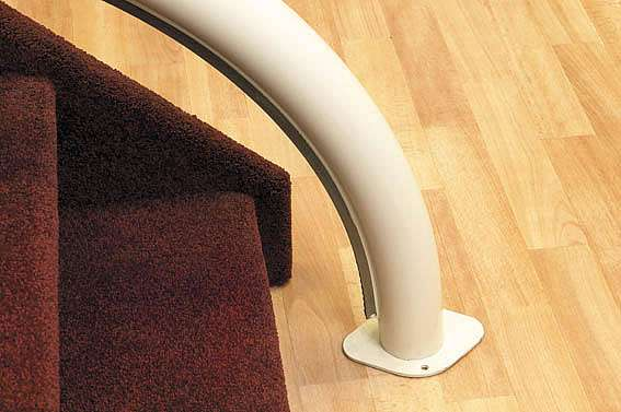 A close-up photo of a Handicare stairlift rail as it connects neatly to the floor at the bottom of the stairs.