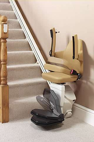 A Handicare Van Gogh stair lift parked at the bottom of the stairs, with time-lapse multiple photo overlays to show how the arm rests, seat, and footrest can be folded up.