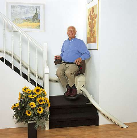 A smiling elderly male user sitting on a Handicare Van Gogh stairlift as it starts to travel up the stairs past the first bend from the bottom of the staircase.