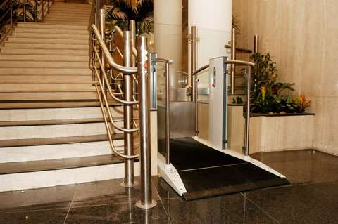 Pollock Lifts Independence Step Lift shown with platform in the down position, situated next to stairs in commercial property in Aldwych, London.