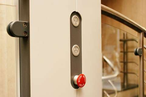 A close-up of a Pollock Lifts Independence Step Lift control buttons: up, down, and emergency stop button, situated inside the lift cubicle.