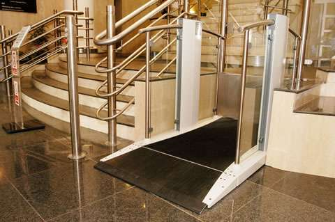 Viewed from the opposite side, a Pollock Lifts Independence Step Lift shown with platform in the down position, situated next to stairs in commercial property in Aldwych, London.