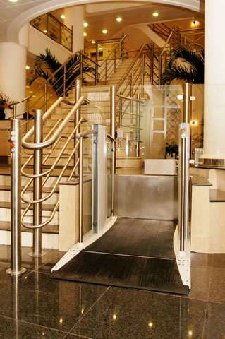 Viewed from the front, a Pollock Lifts Independence Step Lift shown with platform in the down position, situated next to stairs in commercial property in Aldwych, London.