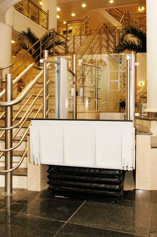 A Pollock Lifts Independence Step Lift shown with platform in the up position meeting the destination floor level 3 or 4 steps higher. Situated next to stairs in commercial property in Aldwych, London.