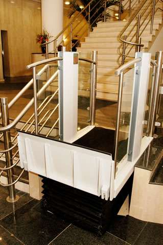 Shown from a different angle and viewed from a higher location, a Pollock Lifts Independence Step Lift shown with platform in the up position meeting the destination floor level 3 or 4 steps higher. Situated next to stairs in commercial property in Aldwych, London.