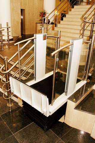 Shown from yet a different angle and viewed from an even higher location, a Pollock Lifts Independence Step Lift shown with platform in the up position meeting the destination floor level 3 or 4 steps higher. Situated next to stairs in commercial property in Aldwych, London.