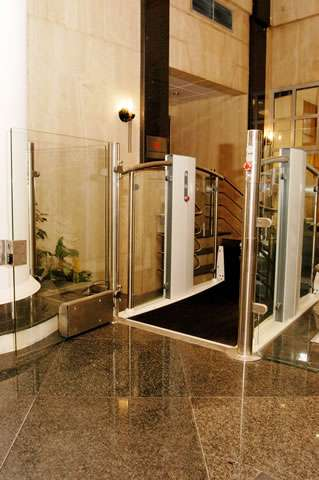 As viewed from the higher destination floor level, a Pollock Lifts Independence Step Lift shown with platform in the up position meeting the destination floor. Situated next to stairs in commercial property in Aldwych, London.