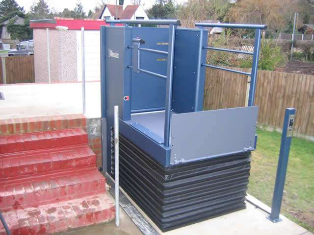 A front angled / side view of Wessex Lifts LR800 low rise lifting platform / step lift with the lift platform in the raised position and wheelchair protection plate raised.