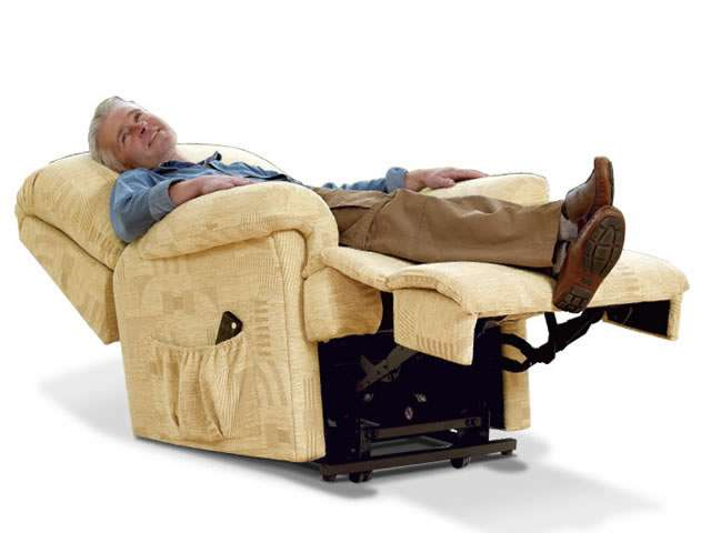 Light beige coloured upholstery Sherborne electric lift rise recliner chair showing an older male user laid back looking relaxed and rested in the chair at the fully reclined position.