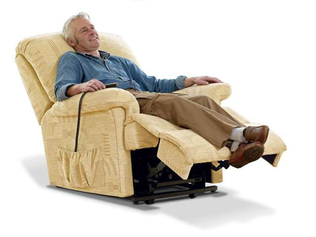 Light beige coloured upholstery Sherborne electric lift rise recliner chair showing an older male user in the chair at the less reclined position.