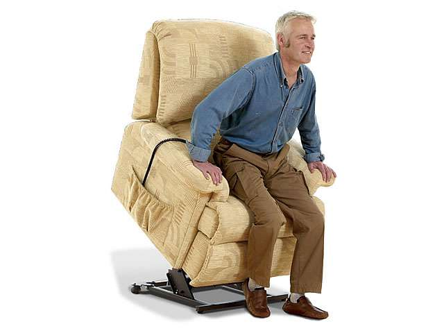 Light beige coloured upholstery Sherborne electric lift rise recliner chair showing an older male user with the chair at the fully lifted up / elevated position, allowing the user to get up from the chair and stand up more easily.