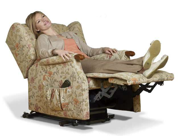 Light pattern coloured upholstery Sherborne electric lift rise recliner chair showing a female user laid back looking relaxed and rested in the chair at the fully reclined position.