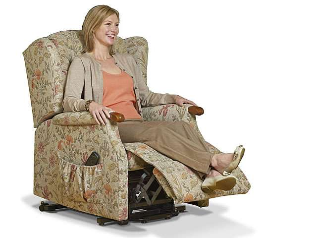 Light patterned coloured upholstery Sherborne electric lift rise recliner chair showing female user in the chair at the less reclined position.