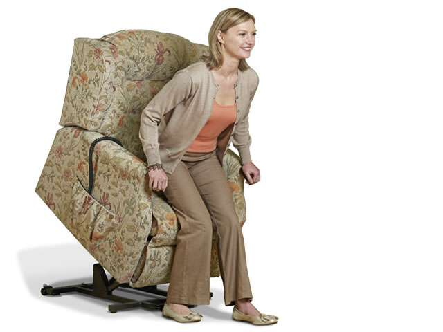 Light patterned coloured upholstery Sherborne electric lift rise recliner chair showing female user with the chair at the fully lifted up / elevated position, allowing the user to get up from the chair and stand up more easily.