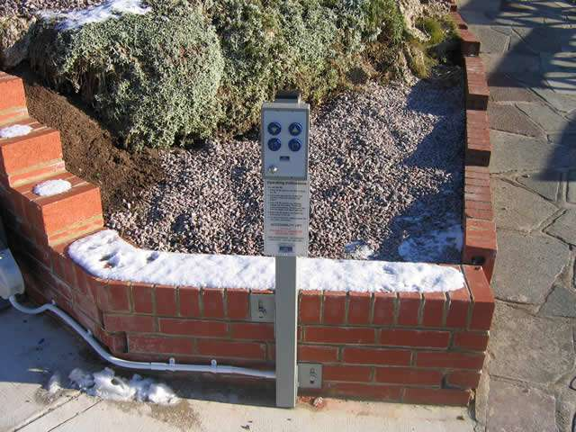 The Express 2 wheelchair lift control panel installed on a custom made metal post at the bottom of the steps.