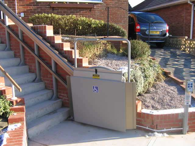 The Express 2 wheelchair lift situated at the bottom of the external steps, and shown with the platform in the folded up position, allowing easy access to the steps for people who do not require the wheelchair platform lift.