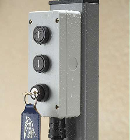 A close-up photo of the wall-mounted control box situated at the bottom of the outside steps. The control box has an up arrow button, down arrow button, and a key inserted into the lock, to allow the user to operate the stair lift. The control box also has some rain speckles on it to show that it is not affected by rain.