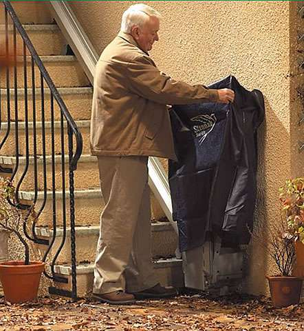 At the bottom of the outside steps, the Stannah 320 outside stairlift is folded up against the wall. The elderly user is placing a rain cover over the folded up stair lift.