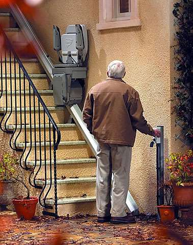 From a different angle than the equivalent earlier photo, a user is standing at the bottom of the outside steps area in which a Stannah 320 stairlift has been installed. The user is pressing a button on the wall-mounted control box, containing the authorisation key, and the folded up stair lift chair is either coming down the steps to the user's position, or the user is sending the stairlift chair up the stairs.