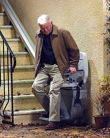 At the bottom of the external building steps, an elderly male user is about to sit on the Stannah 320 outdoor stair lift.