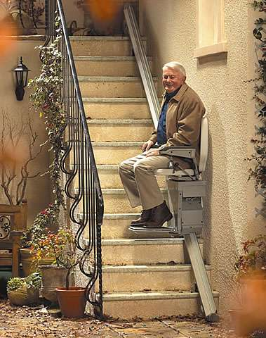 A smiling elderly male user is sitting on the Stannah 320 Outdoor Stairlift, with seatbelt on, either going up or gowing down the stair lift.