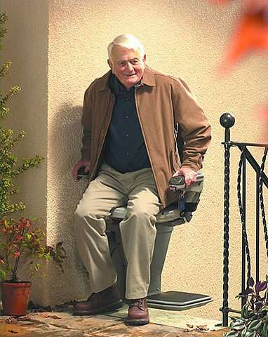 From a different angle, a smiling elderly male user sat on the Stannah 320 outdoor stair lift arriving at the top of external straight stairs. The user has swivelled the stairlft chair safely away from the stairs, thereby using the stairlift chair as a safety barrier, and is about to step on to the outside concrete landing level near the building entry door.