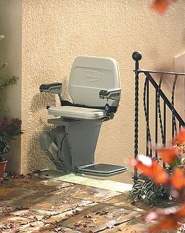 The Stannah 320 Outdoor Stairlift is shown at the top of the steps swivelled to face the concrete landing area. The empty stair lift has  the seat, armrests and footrest in the down position. The stairlift also acts as an additional safety barrier across the outside steps.