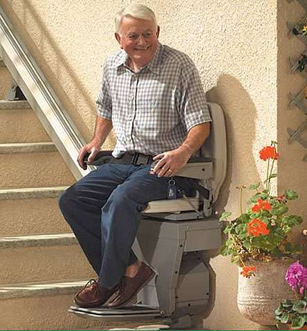 Smiling elderly male user sat on the Stannah 320 outdoor stair lift with seatbelt in closed position, about the be transported up external straight stairs.