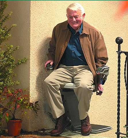 Smiling elderly male user sat on the Stannah 320 outdoor stair lift arriving at the top of external straight stairs. The user has swivelled the stairlft chair away from the stairs and on to the outside concrete landing level near the building entry door.