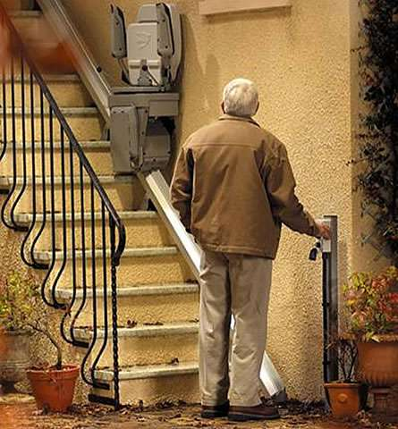 A user standing at the bottom of the outside steps area in which a Stannah 320 stairlift has been fitted. The user is pressing a button on the wall-mounted control box, containing the authorisation key, and the folded up stair lift chair is coming down the steps to the user's position.