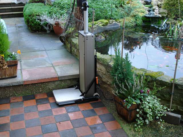 Portable Powerstep lift situated on the bottom step of a garden, to help the user move to the ground next level up and continue walking along the garden path.