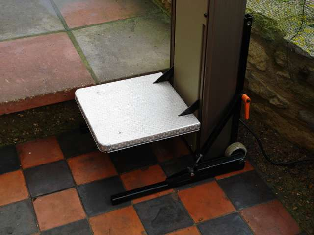 Close-up photo of Portable Powerstep lift situated on the bottom step of a garden walkway, to help the user move to the ground next level up and continue walking along the garden path.